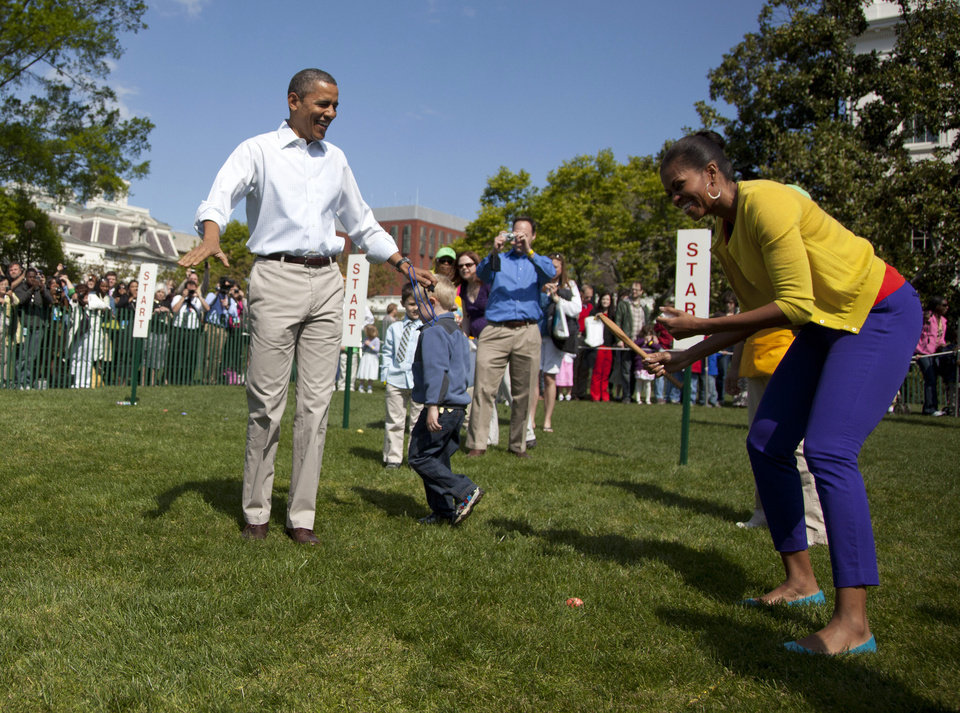 President Barack Obama watches as first lady Michelle Obama competes during the annual Easter Egg Roll race, Monday, April 9, 2012, on the South Lawn of the White House in Washington. (AP Photo/Carolyn Kaster) ORG XMIT: DCCK129