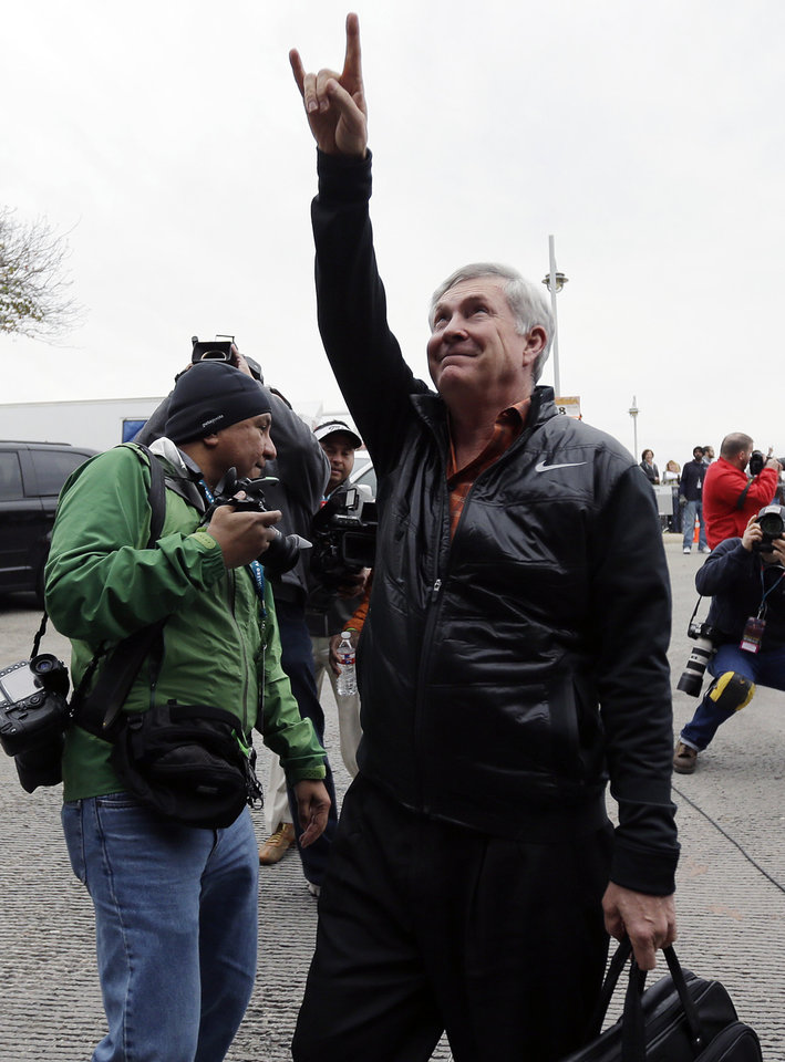 "Texas coach Mack Brown, right, flashes the ""Hook' em Horns"" sign to fans as he arrives for the Valero Alamo Bowl NCAA college football game against the Oregon, Monday,  Dec. 30, 2013, in San Antonio. (AP Photo/Eric Gay)"