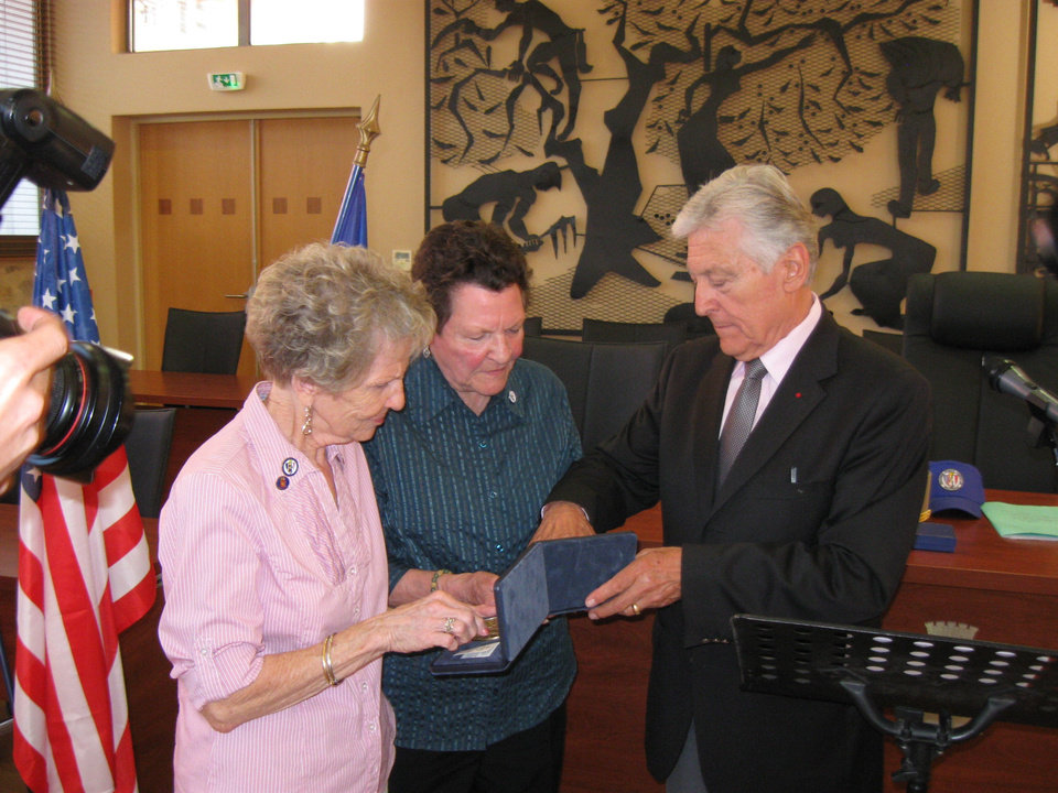 Photo - Gerry Correll, left, of Ponca City, and her sister, Shirley Awalt, of California, receive a medal of honor from Max Piselli, mayor of Draguignan, France, on behalf of their brother, Pfc. James W. Hazen Jr., who was killed Aug. 15, 1944.  PHOTOs PROVIDED BY THE Franco-American Society/ American Battle Monuments Commission