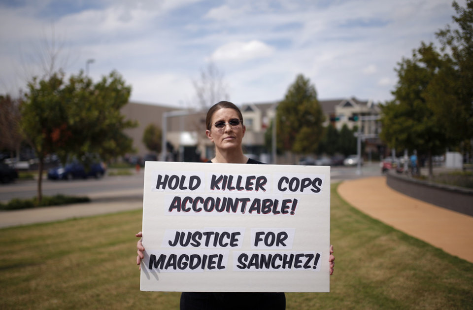 Photo - Amy Bradshaw holds a sign during the Justice for Magdiel Sanchez rally in Oklahoma City, Sunday, Sept. 24, 2017. Photo by Sarah Phipps, The Oklahoman