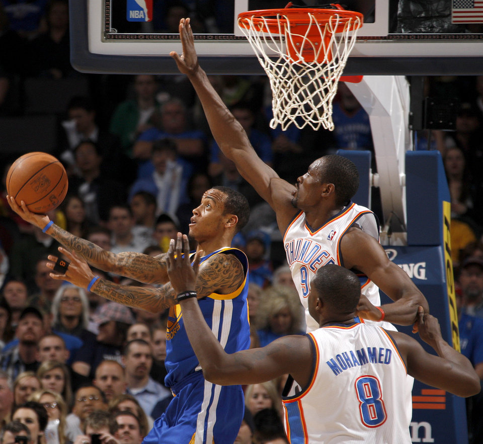 Photo - Oklahoma City's Serge Ibaka (9) and  Nazr Mohammed (8) defend Golden State's Monta Ellis (8) during the NBA basketball game between the Oklahoma City Thunder and the Golden State Warriors at the Oklahoma City Arena, Tuesday, March 29, 2011. Photo by Bryan Terry, The Oklahoman