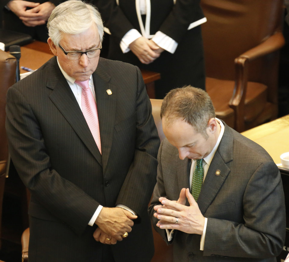 Photo - State Rep. Weldon Watson, Majority Caucus Chair, left and Rep. Jeff Hickman, Speaker Pro Tempore bow their heads during a prayer before Governor Mary Fallin's  State of the State address at the state Capitol in Oklahoma City, Monday February  04, 2013. Photo By Steve Gooch, The Oklahoman