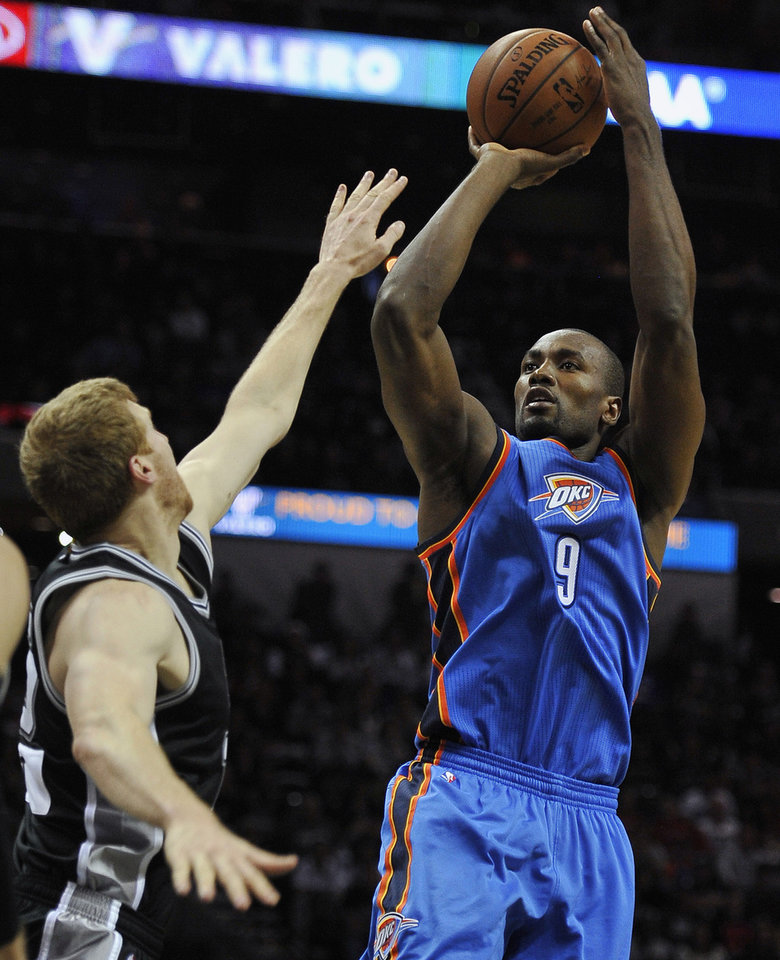 Photo - Oklahoma City Thunder forward Serge Ibaka (9) shoots against San Antonio Spurs forward Matt Bonner during the second half of an NBA basketball game, Thursday, Dec. 25, 2014, in San Antonio. Oklahoma City won 114-106. (AP Photo/Darren Abate)