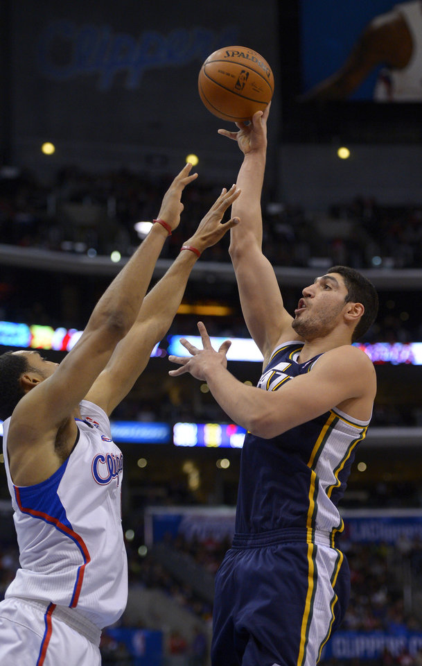 Photo - Utah Jazz center Enes Kanter, right, of Turkey, shoots as Los Angeles Clippers center Ryan Hollins defends during the first half of an NBA basketball game on Saturday, Feb. 1, 2014, in Los Angeles. (AP Photo/Mark J. Terrill)
