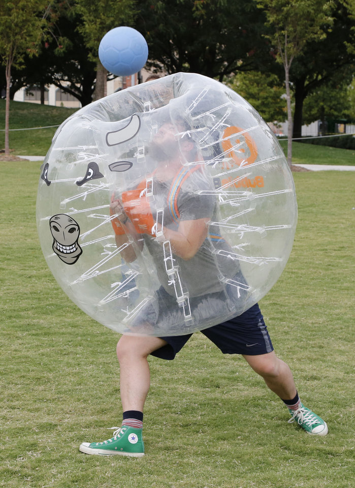 Photo - Oklahoman writer Adam Kemp bounces the ball toward the goal during a BubbleBall soccer match at the Myriad Gardens in Oklahoma City, OK, Friday, October 16, 2015,  Photo by Paul Hellstern, The Oklahoman