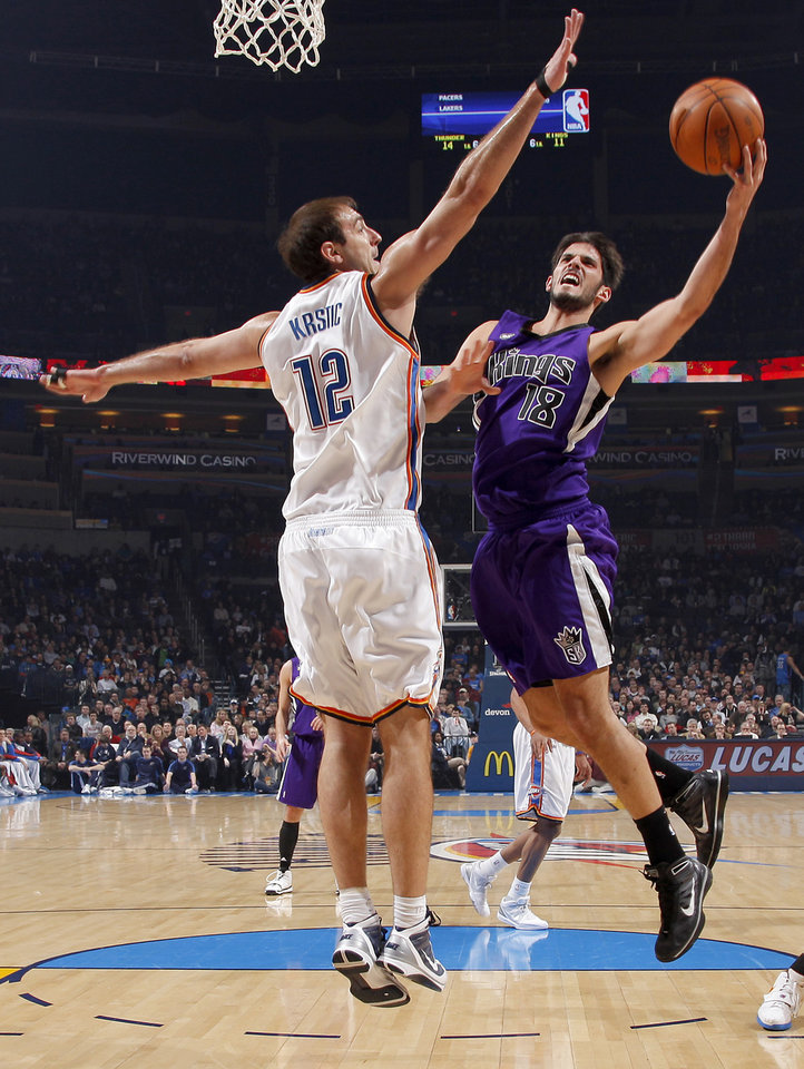 Photo - Oklahoma City's Nenad Krstic defends Sacramento's Omri Casspi during the NBA basketball game between the Oklahoma City Thunder and the Sacramento Kings at the Ford Center in Oklahoma City, Tuesday, March 2, 2010.  Photo by Bryan Terry, The Oklahoman ORG XMIT: KOD