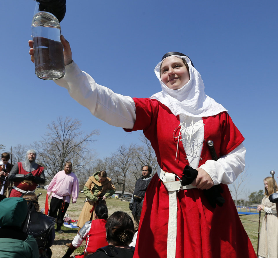 Photo -  Jessie Smith gives a fellow cast member water during a Medieval Fair rehearsal in Reaves Park. The fair opens Friday and continues through Sunday. PHOTO BY STEVE SISNEY, THE OKLAHOMAN   STEVE SISNEY -