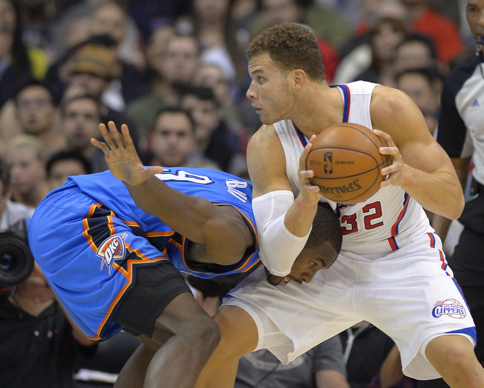 Photo - Los Angeles Clippers forward Blake Griffin, right, gets Oklahoma City Thunder forward Serge Ibaka, of Congo, in a head lock as he drives toward the basket during the second half of their NBA basketball game, Tuesday, Jan. 22, 2013, in Los Angeles. The Thunder won 109-97.  (AP Photo/Mark J. Terrill)  ORG XMIT: LAS108