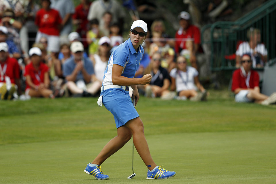 Photo - Europe's Carlota Ciganda, from Spain, sinks a birdie putt on the 15th hole against United States' Morgan Pressel in their singles match at the Solheim Cup golf tournament on Sunday, Aug. 18, 2013, in Parker, Colo. (AP Photo/David Zalubowski)