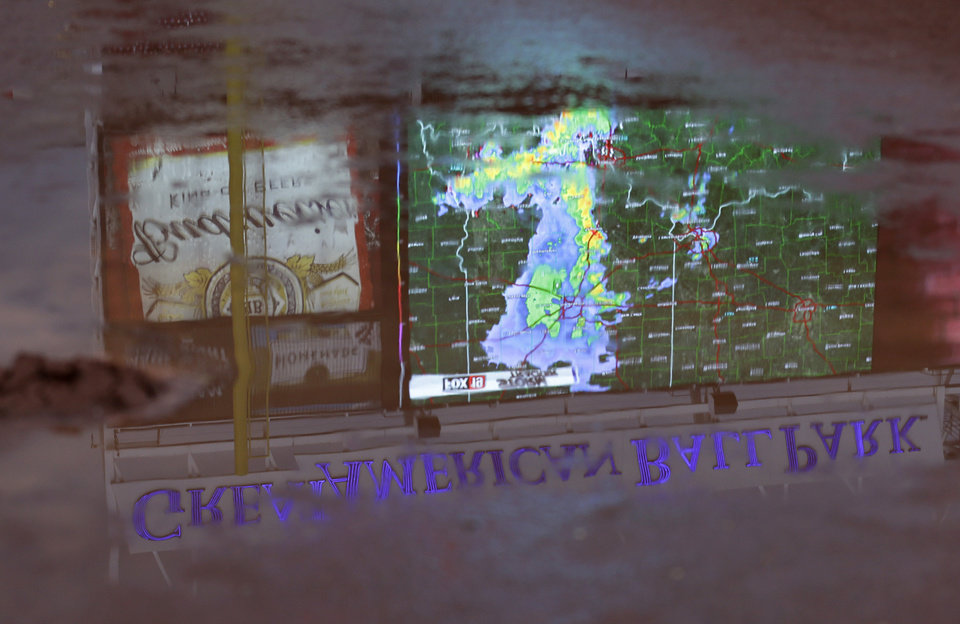 Photo - Weather radar being shown on the scoreboard at Great American BallPark is reflected in a pool of water on the field prior to a baseball game between the Cincinnati Reds and the Atlanta Braves being delayed by rain, Saturday, Aug. 23, 2014, in Cincinnati. (AP Photo/Al Behrman)