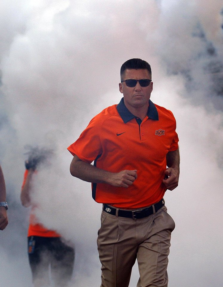 Photo - Oklahoma State head coach Mike Gundy runs onto the field during a college football game between Oklahoma State University (OSU) and Savannah State University at Boone Pickens Stadium in Stillwater, Okla., Saturday, Sept. 1, 2012. Photo by Sarah Phipps, The Oklahoman