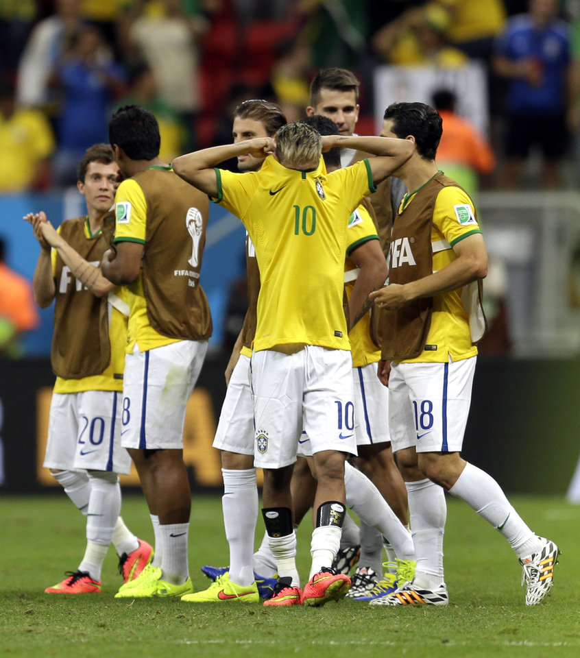 Photo - Brazil's Neymar takes his shirt off following their 4-1 victory over Cameroon in the group A World Cup soccer match between Cameroon and Brazil at the Estadio Nacional in Brasilia, Brazil, Monday, June 23, 2014. (AP Photo/Natacha Pisarenko)