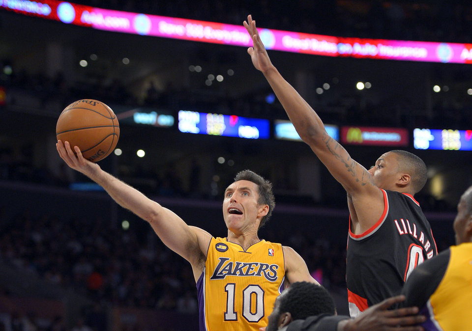 Photo - Los Angeles Lakers guard Steve Nash, left, puts up a shot as Portland Trail Blazers guard Damian Lillard defends during the first half of their NBA basketball game, Friday, Feb. 22, 2013, in Los Angeles. (AP Photo/Mark J. Terrill)