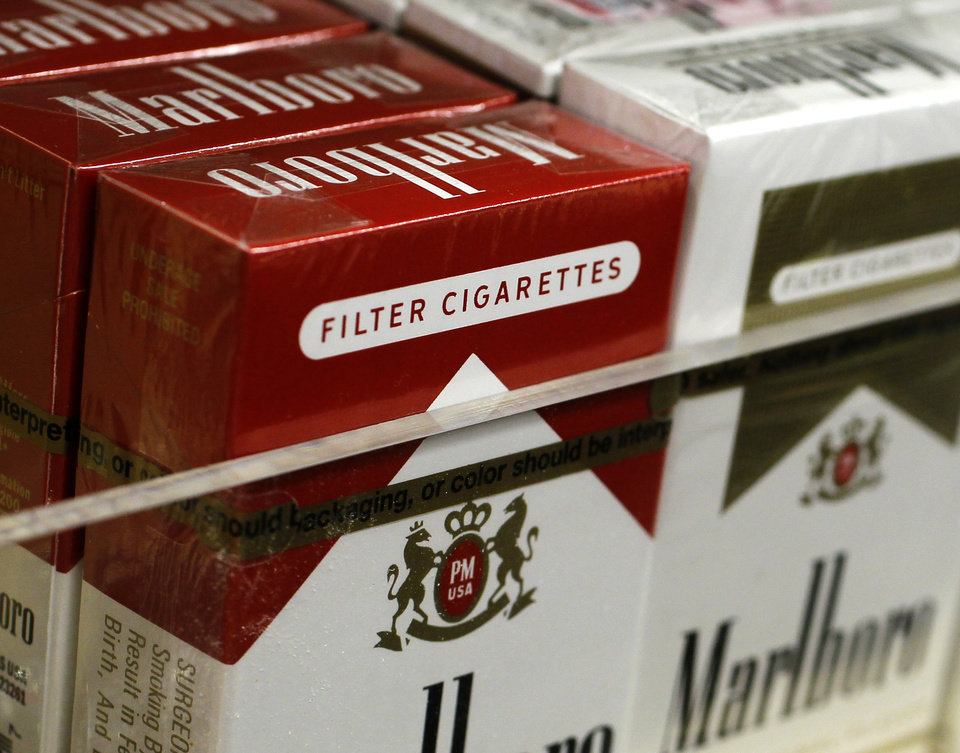 Photo - Pictured are packs of cigarettes waiting to be purchased at a Chicago area news stand Friday, Nov. 30, 2012. New tobacco products have come nearly to a halt in the U.S. because regulatory reviews for thousands of applications required by a 2009 law are taking much longer than the law requires. Though it might sound like good news from a health perspective, the halt demonstrates how tricky it is to start regulating an industry.(AP Photo/Charles Rex Arbogast)