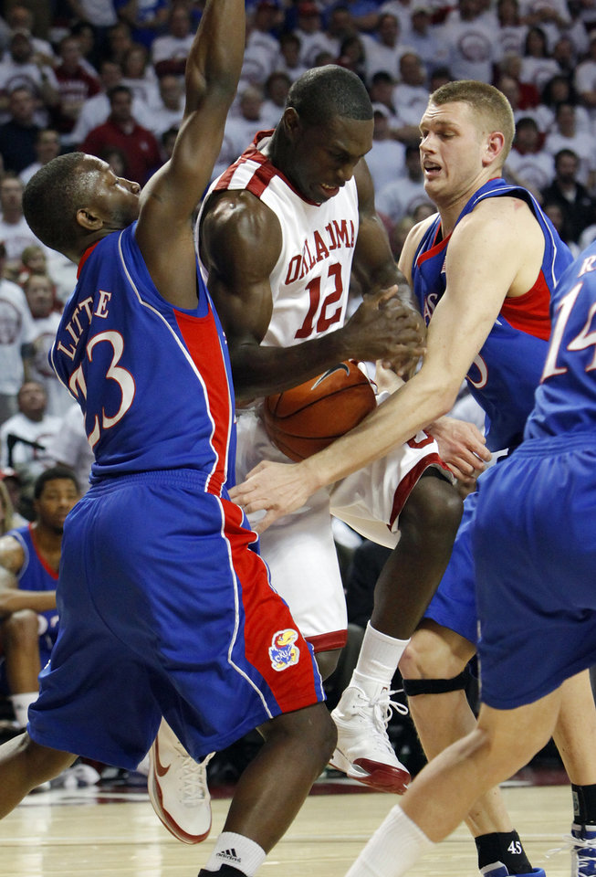 Photo - OU's Juan Pattillo (12) gets caught between KU's Mario Little (23) and Cole Aldrich (45) in the first half of the men's college basketball game between Kansas and the University of Oklahoma at the Lloyd Noble Center in Norman, Okla., Monday, February 23, 2009. BY NATE BILLINGS, THE OKLAHOMAN ORG XMIT: KOD