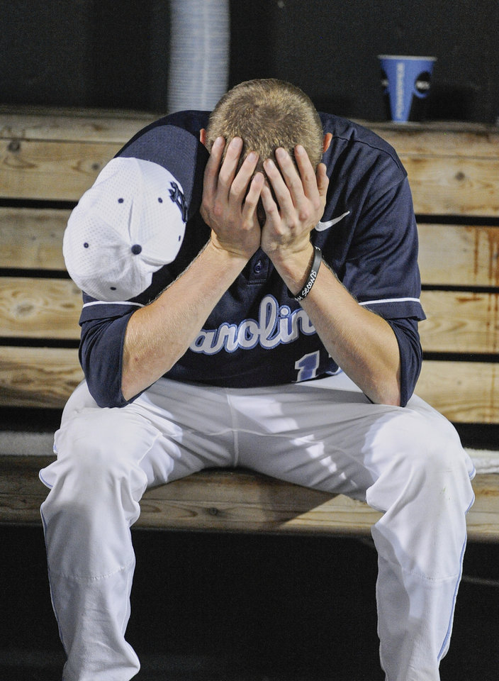 North Carolina's Chris McCue sits in the dugout after losing 4-1 to UCLA in an NCAA College World Series baseball game in Omaha, Neb., Friday, June 21, 2013. UCLA won 4-1. (AP Photo/Eric Francis)