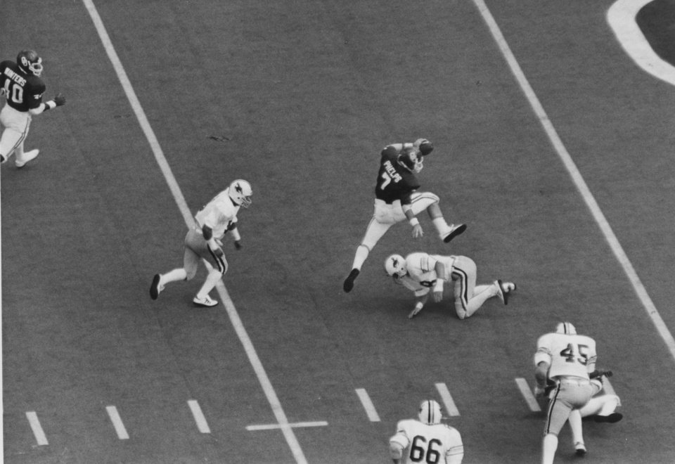 "Photo - FOOTBALL OU UNIVERSITY OF OKLAHOMA 1981B 44: Caption reads ""Starting OU quarterback Kelly Phelps hurdles a Wyoming defender at the three and completes a seven-yard touchdown run during second-quarter action Saturday."" Photo taken by Al McLaughlin. Date photo was taken unknown. Photo was published in The Daily Oklahoman 9-13-1981."