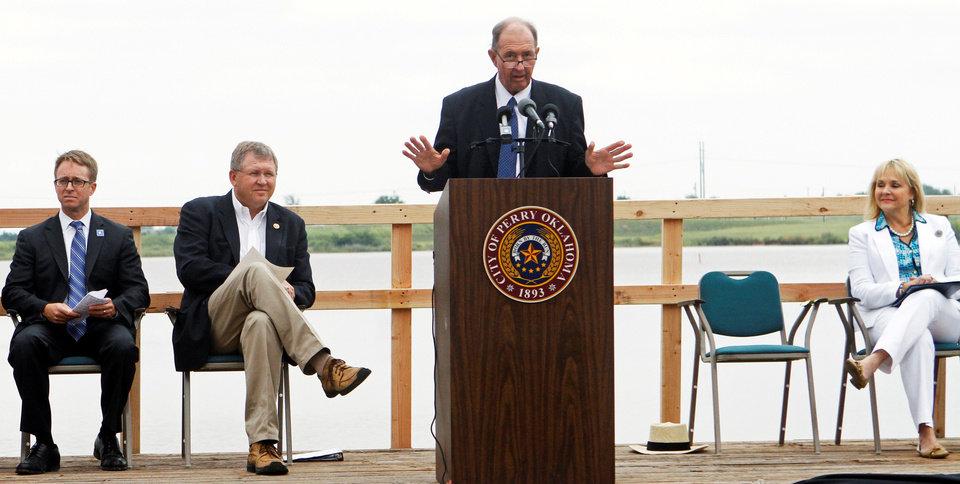 Photo - Mike Thralls, executive director of the Oklahoma Conservation Commission, speaks Friday at the announcement ceremony for the Oklahoma watershed program. Among others at the ceremony are, from left, Jason Weller, chief of the Natural Resources Conservation Service, U.S. Rep. Frank Lucas and Gov. Mary Fallin.
