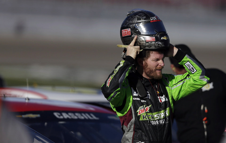 Photo - Dale Earnhardt Jr. puts on his helmet during qualifying for Sunday's NASCAR Sprint Cup Series auto race on Friday, March 7, 2014, in Las Vegas. (AP Photo/Isaac Brekken)