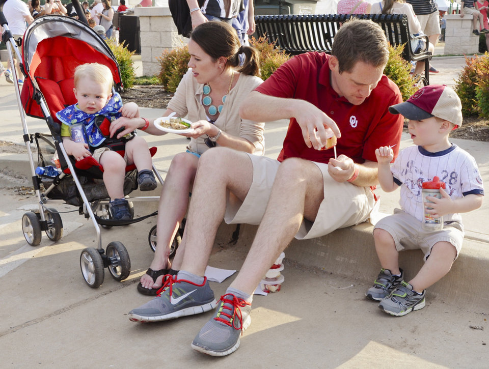 Photo - Rook, Jodi, Brent and Cash Dishman, from left,  try the offerings they found at Taste of Edmond, one of the activities during the LibertyFest Fourth of July celebrations. PHOTO BY M. TIM BLAKE, FOR THE OKLAHOMAN.  M. Tim Blake - FOR THE OKLAHOMAN
