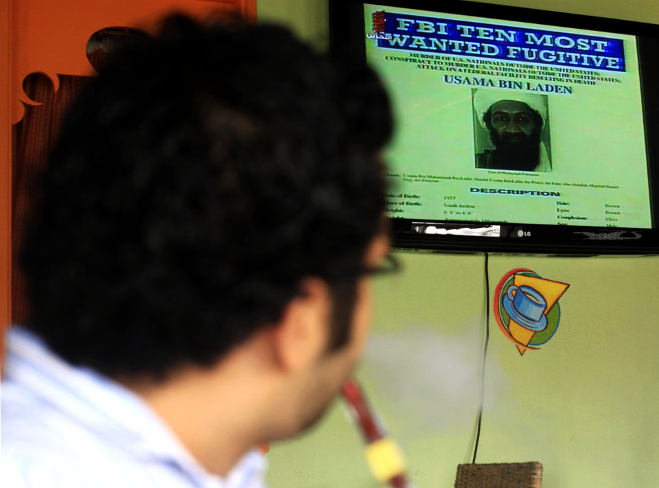 Photo - Bahraini man smokes a water-pipe and watches a TV news report on the killing of Al-Qaida leader Osama bin Laden,  at a coffee shop in Sitra, Bahrain, on Monday, May 2, 2011.   al-Qaida chief  Osama bin Laden was slain at a fortress-like compound in Abbottabad, Pakistan, early Monday in a firefight with U.S. forces, ending a manhunt that spanned a decade. (AP Photo/Hasan Jamali) ORG XMIT: XHJ101