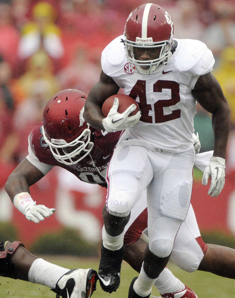Photo -   Alabama running back Eddie Lacy (42) eludes Arkansas defensive tackle Robert Thomas during the first half of an NCAA college football game in Fayetteville, Ark., Saturday, Sept. 15, 2012. (AP Photo/David Quinn)