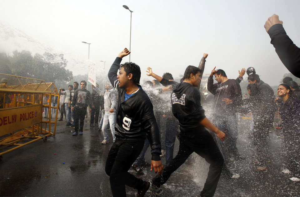 Indian protesters shout slogans as policemen use water cannon to disperse those demonstrating against a gang rape and brutal beating of a 23-year-old student on a bus, in New Delhi, India, Sunday, Dec. 23, 2012. The attack last Sunday has sparked days of protests across the country. (AP Photo/Tsering Topgyal)