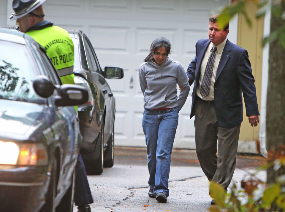 Photo - FILE - In this Sept. 28, 2012 file photo, Annie Dookhan, center, is escorted to a cruiser outside her home in Franklin, Mass. Dookhan is accused of faking drug results, forging signatures and mixing samples a state police lab. State police say Dookhan tested more than 60,000 drug samples involving 34,000 defendants during her nine years at the lab in one of Massachusetts's top stories in 2012.  (AP Photo/Bizuayehu Tesfaye, File)