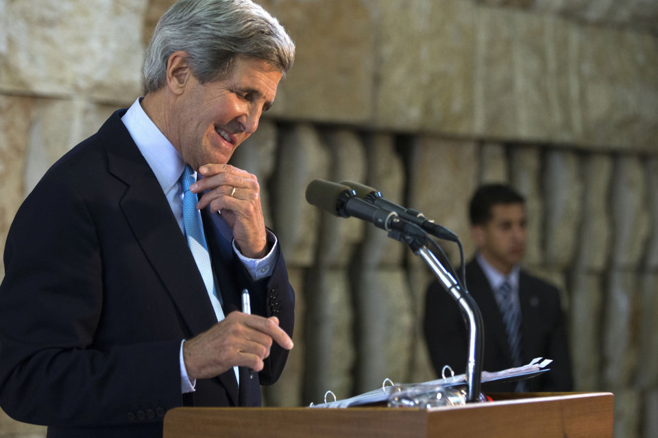 Photo - U.S. Secretary of State John Kerry smiles at a question from a reporter during a news conference about his trip to the Middle East, in Tel Aviv, Israel on Sunday, June 30, 2013. Kerry engaged in breakneck shuttle diplomacy to coax Israel and the Palestinians back into peace talks over a four-day span with multiple trips to Jordan and Israel and a stop in the West Bank town of Ramallah. (AP Photo/Jacquelyn Martin, Pool)