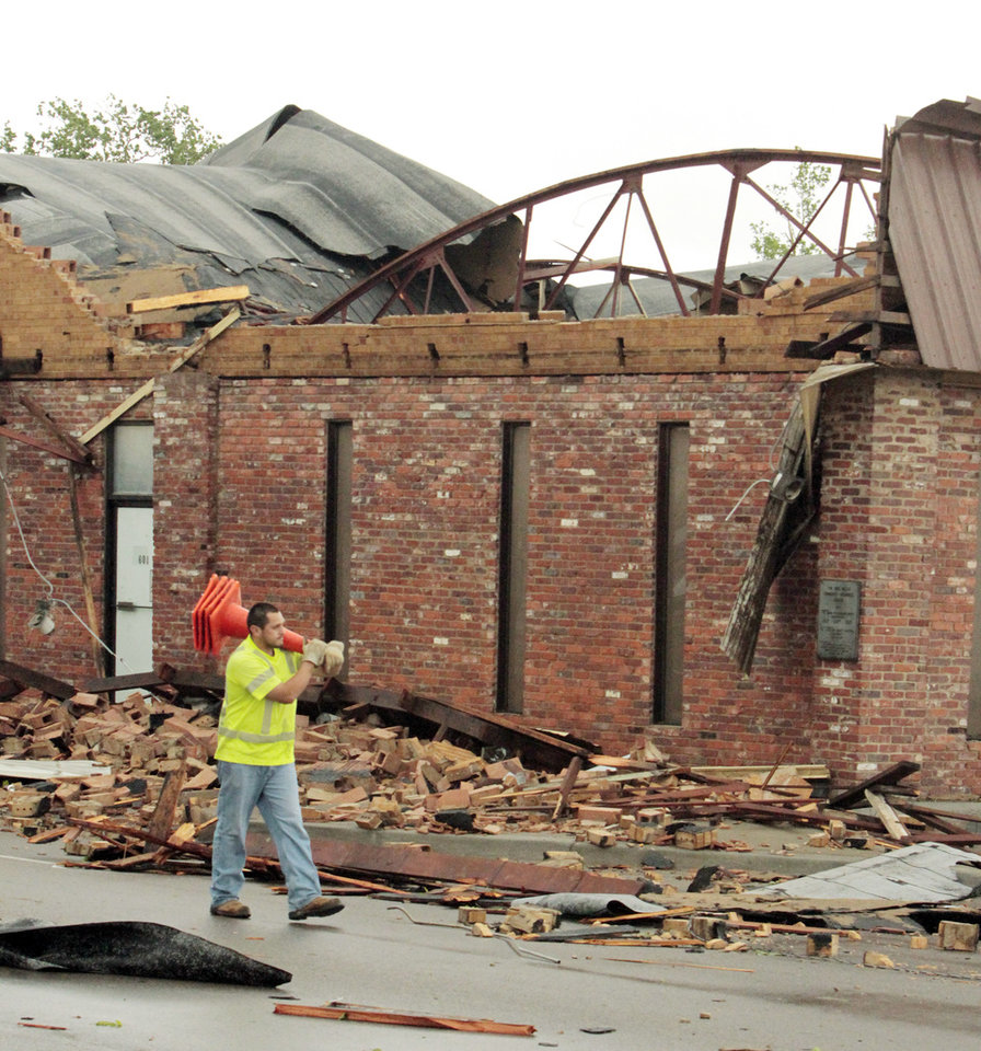 Photo - The roof of this business at Porter and Hughbert was blown into the street closing Porter after a reported tornado that struck the west and central pars of town on Friday, April 13, 2012, in Norman, Okla.  Photo by Steve Sisney, The Oklahoman