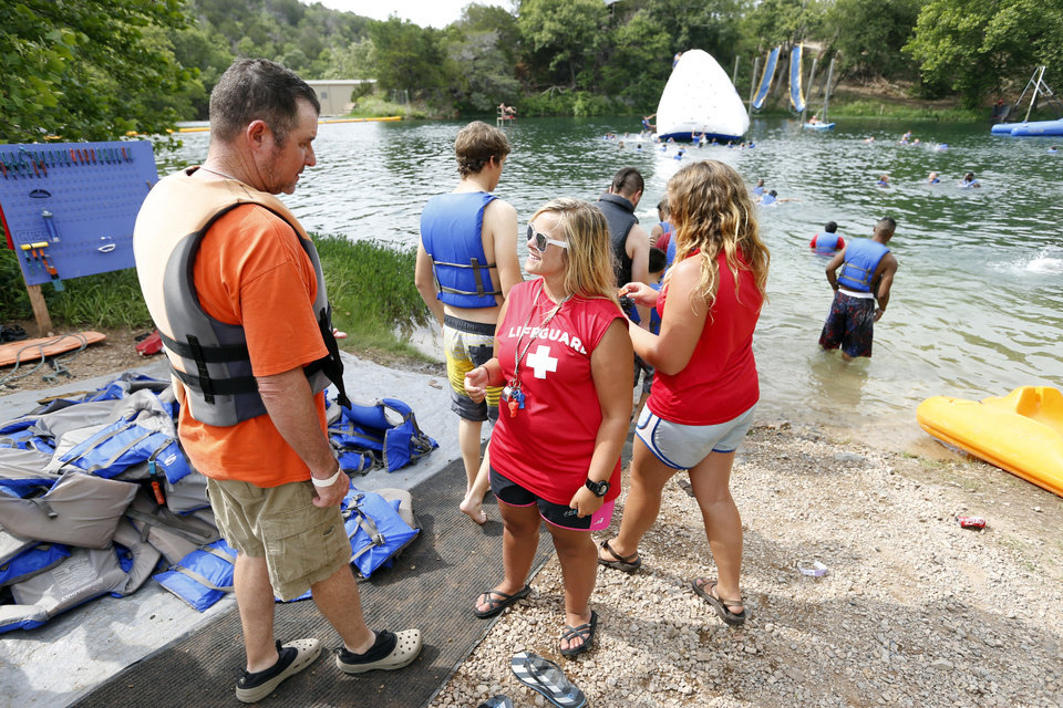 Staffer Abbie Paty checks safety equipment as male campers and sponsors enter Baptist Lake at Falls Creek Youth Camp on Tuesday, June 25, 2013 in Davis, Okla.  Photo by Steve Sisney, The Oklahoman