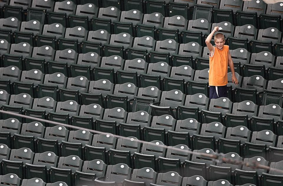 Photo -  A baseball fan takes refuge under a small piece of paper as he tries to stay dry in the rain delay during the third game of the Big 12 Baseball Championship between Kansas State and Baylor at the Bricktown Ballpark on Wednesday, May 26, 2010, in Oklahoma City, Okla.  Photo by Chris Landsberger, The Oklahoman