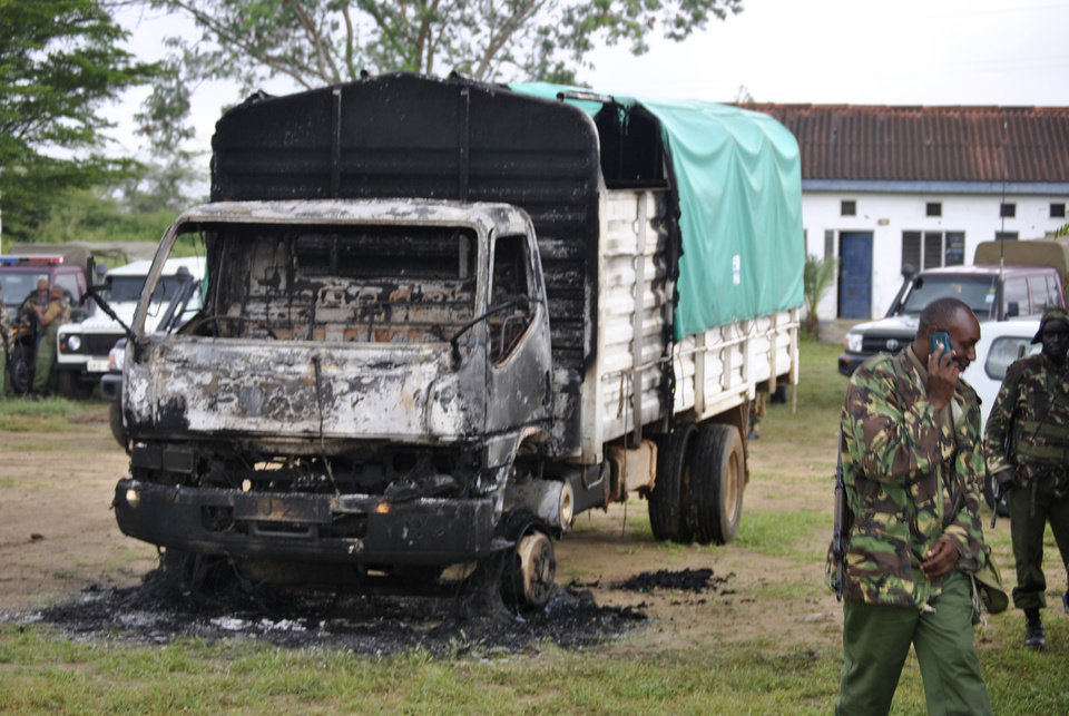 Photo - Policemen stand near the wreckage of a burnt vehicle after gunmen attacked, outside Gamba police station in Gamba, Kenya, Sunday, July 6, 2014. Eighteen people were killed in overnight attacks by the gunmen in two counties on the Kenyan coast, where last month al-Qaida-linked militants claimed responsibility for killing 65 people, the Kenya Red Cross said Sunday. The Sunday attacks took place in the towns of Hindi in Lamu county and Gamba in Tana River, the Kenya Red Cross chief Abbas Gulet said. Al-Qaida-linked al-Shabab militants from Somalia claimed responsibility for the attacks. (AP Photo)