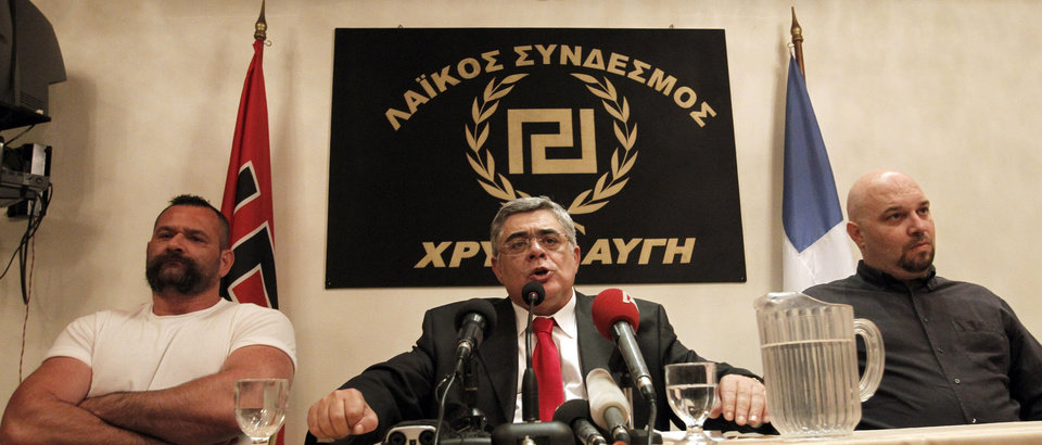 Photo -   Golden Dawn leader Nikolaos Michaloliakos, center, speaks during a news conference in front of a banner with the twisting Maeander, an ancient Greek decorative motif that the party has adopted as its symbol in Athens, Sunday, May 6, 2012. The far-right Golden Dawn party is set to win as much as 8 percent of the vote, according to exit polls, as Greeks punished traditionally dominant parties that backed harsh austerity measures tied to debt relief agreements. (AP Photo/Petros Giannakouris)