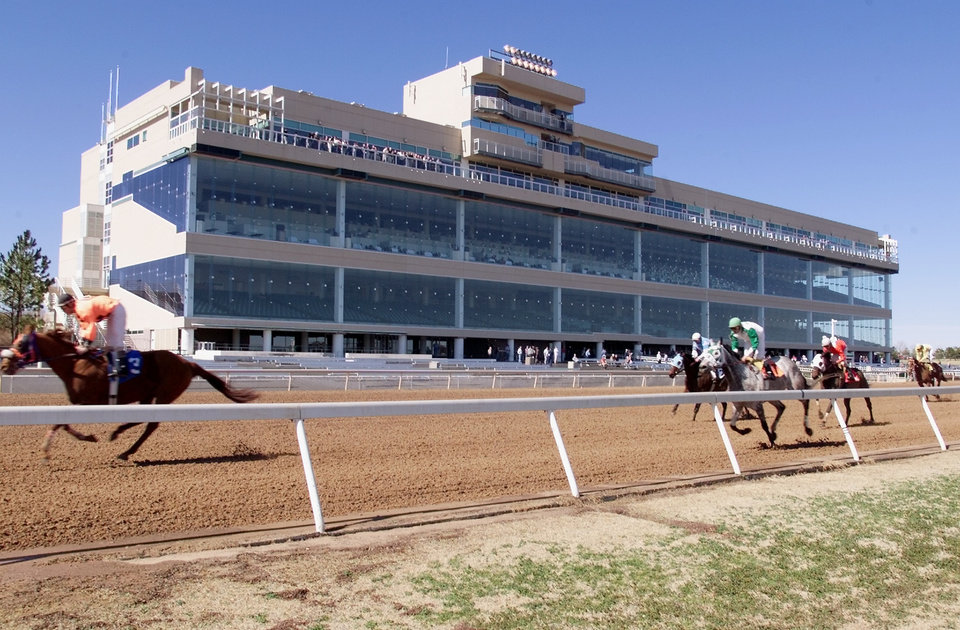 Photo - Thoroughbred horses finish the first race Friday afternoon in front of the grandstand at Remington Park Racetrack in NE OKC.