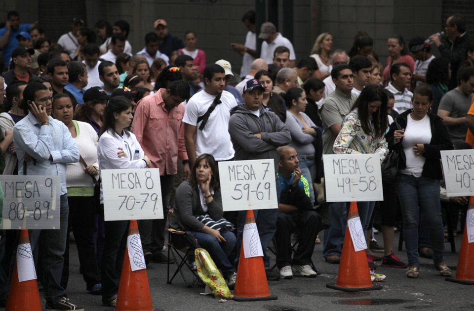 People wait in line to vote in the presidential election at a polling station in Caracas, Venezuela, Sunday, Oct. 7, 2012. President Hugo Chavez is running against opposition candidate Henrique Capriles. (AP Photo/Ramon Espinosa)