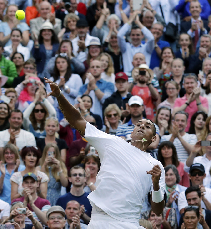 Photo - Nick Kyrgios of Australia throw a tennis ball into the crowd as he celebrates defeating Rafael Nadal of Spain in their men's singles match at the All England Lawn Tennis Championships in Wimbledon, London, Tuesday July 1, 2014. (AP Photo/Ben Curtis)