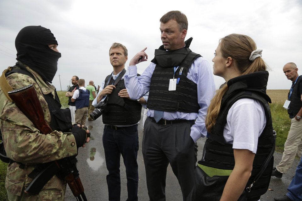 Photo - Representatives from the Organization for Security and Cooperation speak to a pro-Russia fighter at the crash site of a Malaysia Airlines jet near the village of Hrabove, Friday, July 18, 2014. Representatives from the Organization for Security and Cooperation in Europe and four Ukrainian experts had traveled into rebel-controlled areas to begin an investigation into the attack that killed 298 people from nearly a dozen nations. (AP Photo/Dmitry Lovetsky)