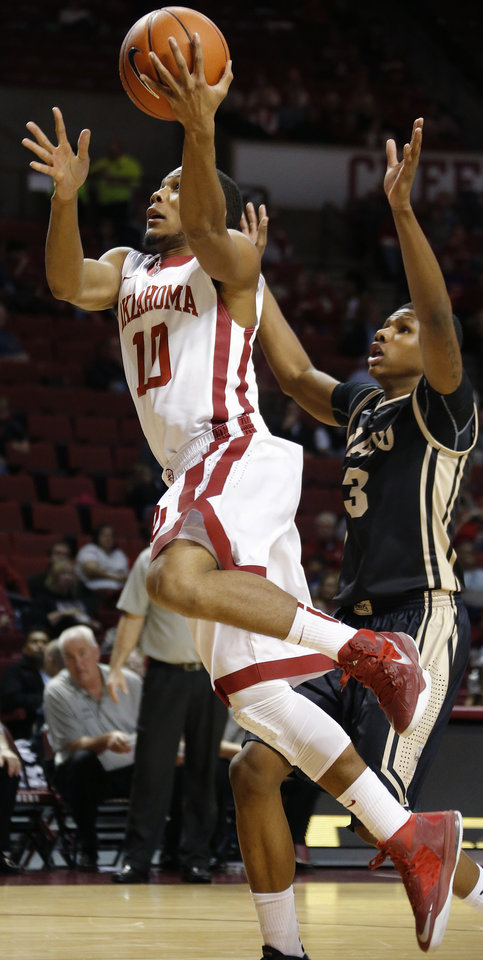 Photo - Oklahoma's Jordan Woodard (10) goes past Idaho's Perrion Callandret (3) during a college basketball game between the University of Oklahoma Sooners and the Idaho Vandals at Lloyd Noble Center in Norman, Okla., on Wednesday, Nov. 13, 2013. Wednesday, Nov. 13, 2013. Photo by Bryan Terry, The Oklahoman
