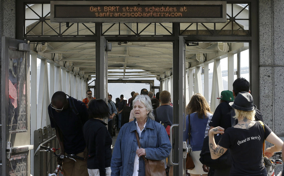 Commuters board a San Francisco Bay Ferry leaving for Oakland as passengers arrive from a ferry from Alameda at the Ferry Terminal in San Francisco, Tuesday, July 2, 2013. San Francisco Bay area commuters endured another tough morning commute on Tuesday, as a strike by workers for a heavily used train system entered its second day. Lines for ferries and buses appeared even longer than on Monday, and BART said charter buses it was running at four stations reached capacity before 7 a.m. and could not accommodate additional passengers. (AP Photo/Jeff Chiu)
