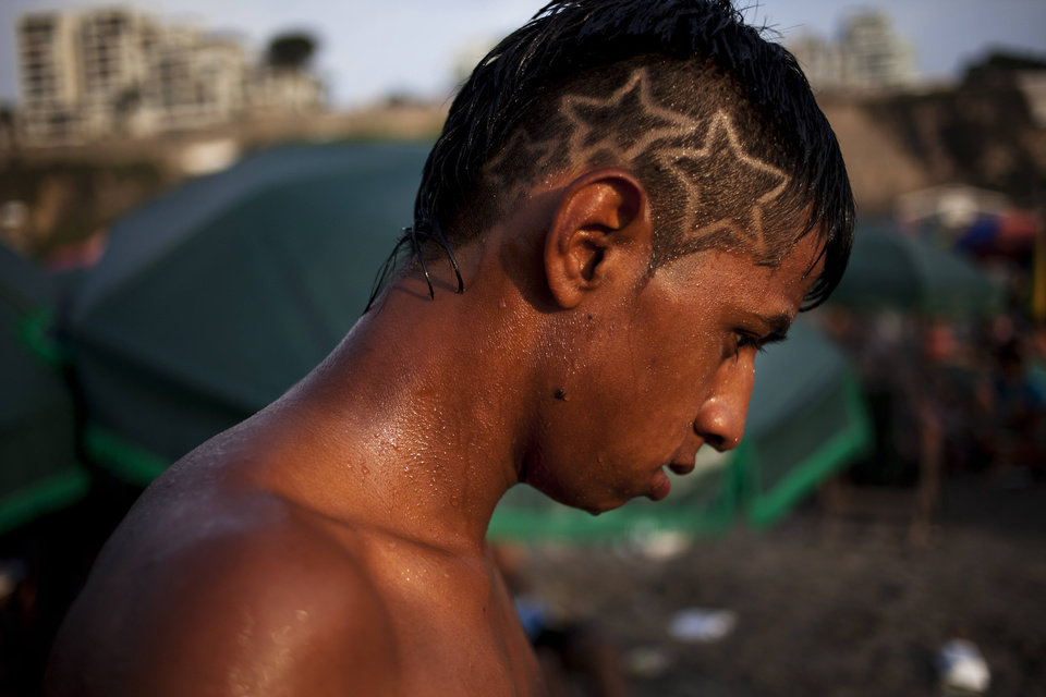 Photo - In this March 3, 2013 photo, Giovani Camargo dries off after a swim in the waters of Agua Dulce beach in Lima, Peru. While Lima's elite spends its summer weekends in gate beach enclaves south of the Peruvian capital, the working class jams by the thousands on a single municipal beach of grayish-brown sands and gentle waves. The only barrier to entry to Agua Dulce beach is two dollars, the price of bus fare to get there and home. (AP Photo/Rodrigo Abd)