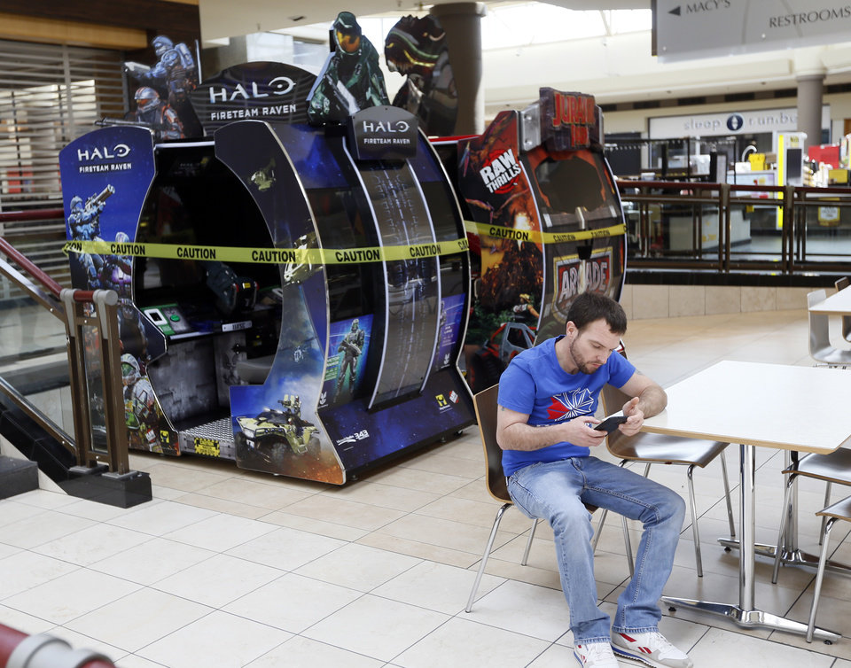 Photo - Video games are taped off because they are high-touch surfaces at Penn Square Mall during the re-opening of the mall after being closed because of the coronavirus pandemic, in Oklahoma City, Friday, May 1, 2020. [Nate Billings/The Oklahoman]