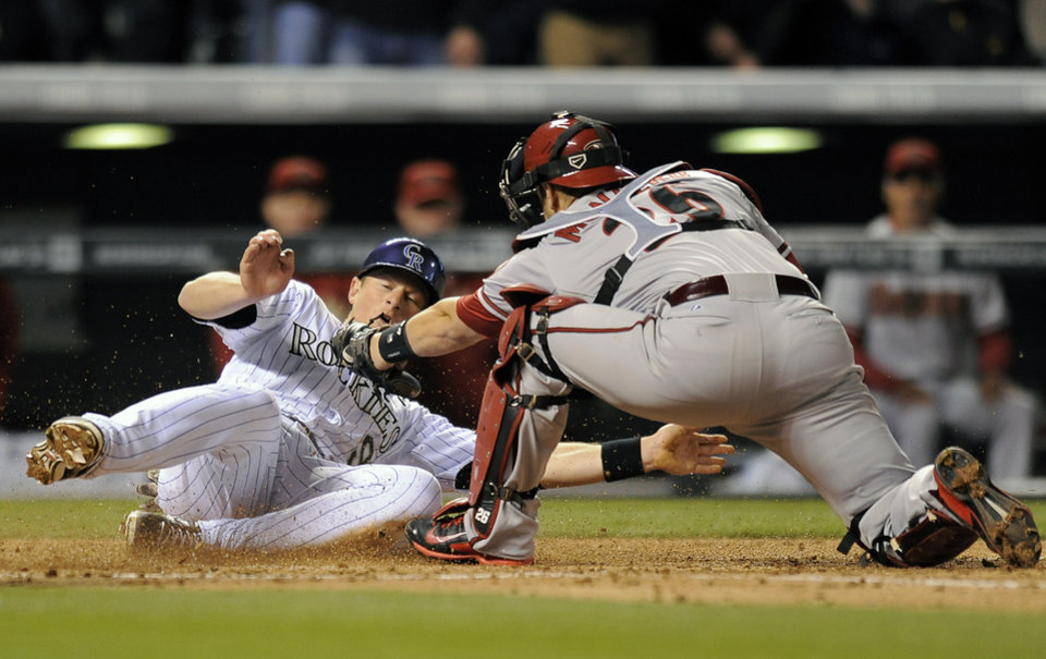Photo - Colorado Rockies DJ LeMahieu, left, slides safely past the tag by Arizona Diamondbacks catcher Miguel Montero, right, to score in the fifth inning of a baseball game Saturday, April 5, 2014, in Denver. (AP Photo/Chris Schneider)