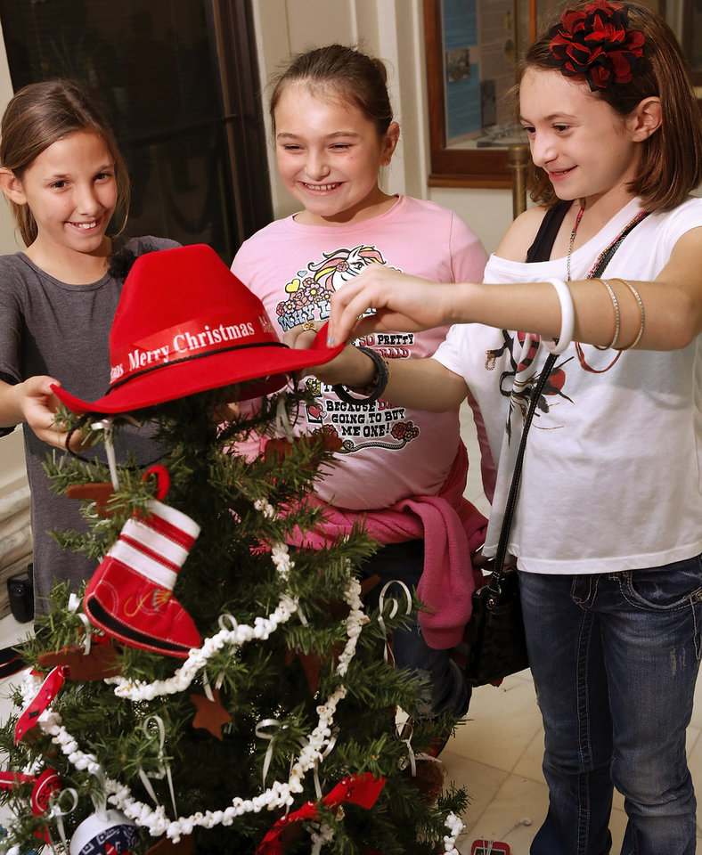 From left, Asher Elementary School fourth and fifth grade students Victoria Frankovich, Madilynn Larman and Malorie Larman  place a red cowboy hat atop their school's decorated tree. The theme of their tree is  'A Cowboy Western Christmas.'  School children from across the state came to the state Capitol  to decorate 36  small Christmas trees in the hallways and rotunda.  Gov. Mary Fallin and State Superintendent Janet Barresi joined Santa Claus in greeting the students at each tree after they were decorated. Many of the children stayed to watch the  governor light the state Christmas tree on the south plaza on Thursday,  Nov. 29, 2012.   Photo by Jim Beckel, The Oklahoman