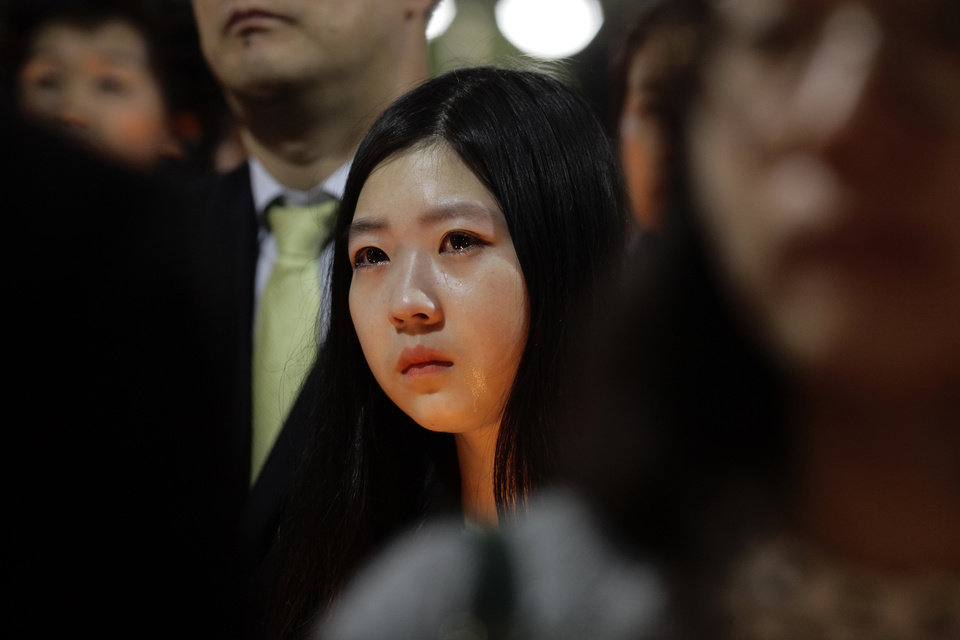 Photo - A woman joins candlelight vigil for the missing passengers of a sunken ferry at Danwon High School in Ansan, South Korea, Thursday, April 17, 2014. An immediate evacuation order was not issued for the ferry that sank off South Korea's southern coast, likely with scores of people trapped inside, because officers on the bridge were trying to stabilize the vessel after it started to list amid confusion and chaos, a crew member said Thursday.  (AP Photo/Wonghae Cho)