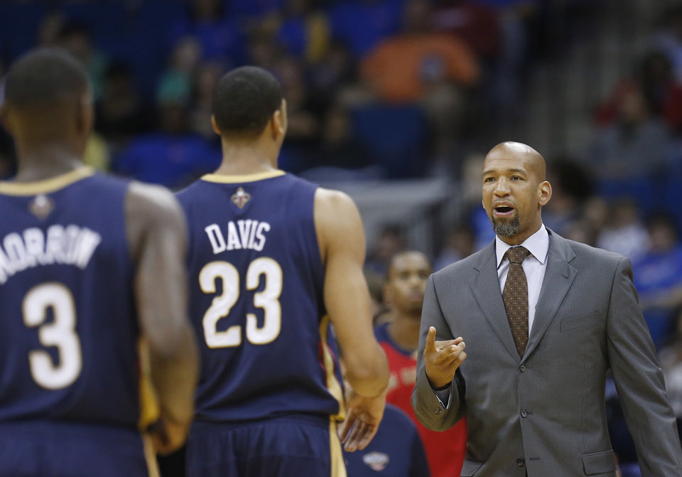 New Orleans Pelicans coach Monty Williams, right, talks with Anthony Davis (23) and Anthony Morrow (3) in the second quarter of an NBA basketball preseason game against the Oklahoma City Thunder in Tulsa, Okla., Thursday, Oct. 17, 2013. (AP Photo/Sue Ogrocki) ORG XMIT: OKSO114