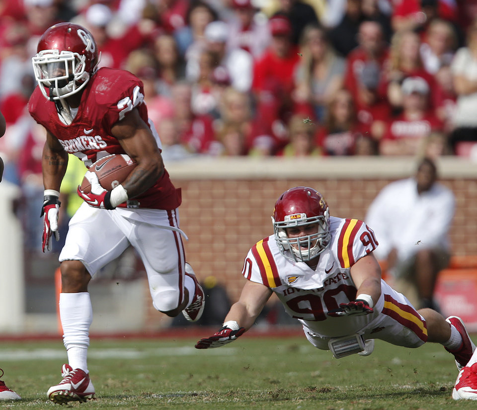 Oklahoma's Brennan Clay (24) runs past Iowa State's Mitchell Meyers (90) during the college football game between the University of Oklahoma Sooners (OU) and the Iowa State University Cyclones (ISU) at Gaylord Family-Oklahoma Memorial Stadium in Norman, Okla. on Saturday, Nov. 16, 2013. Photo by Chris Landsberger, The Oklahoman