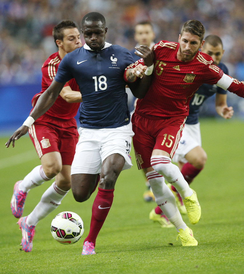 Photo - France's Moussa Sissoko, left, battles with Spain's Sergio Ramos during their international friendly soccer match at the Stade de France in Saint Denis, outside Paris, Thursday, Sept. 4, 2014. (AP Photo/Christophe Ena)