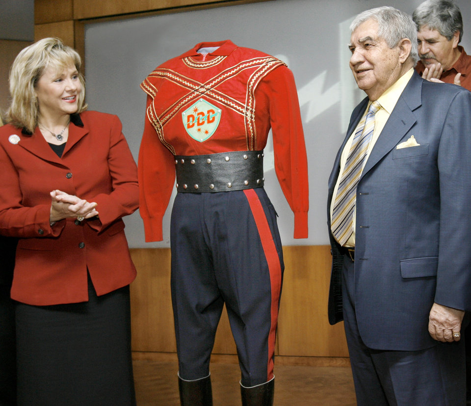 Photo - Lt. Gov. Mary Fallin joins with the crowd in applause after helping Oklahoma City radio and television pioneer Danny Williams unveil an original costume worn by him when he played the role of 3-D Danny for WKY-TV in the early days of television in Oklahoma. The costume was donated to the Oklahoma History Center during a ceremony in Oklahoma City on Monday, March 13, 2006. by  Jim Beckel/The Oklahoman.