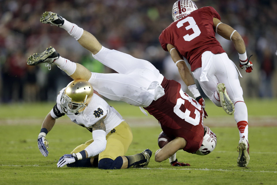Photo - Stanford tight end Davis Dudchock (83) leaps over Notre Dame cornerback Bennett Jackson, bottom left, after a reception during the first half of an NCAA college football game on Saturday, Nov. 30, 2013, in Stanford, Calif. (AP Photo/Marcio Jose Sanchez)